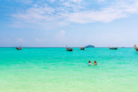 Two unidentifiable girls are snorkeling at Ko Lipe island, Thailand. Turquoise sea, pure water and coral reef with many tropical and exotic animals.