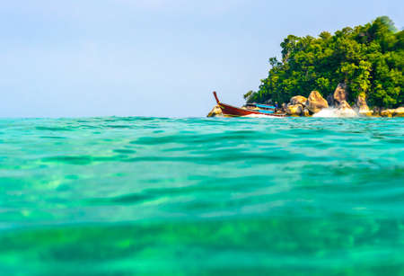View from sea, long tail boat is moving from small island at Koh Lipe. Vibrant turquoise sea, small island with rock in background. Concept of tropical paradise.