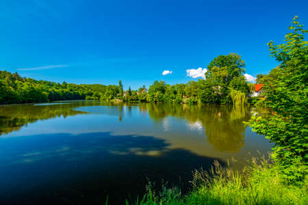 Small lake and fish pond near Mnisek pod Brdy chateau. Summer day with blue sky. Фото со стока