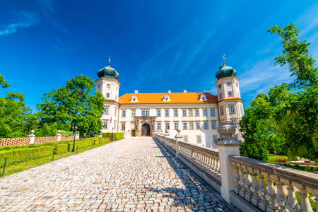 Historical chateau at Mnisek pod Brdy city, Czech Republic. View of ancient building with towers, built in gothic style. Sunny summer day, blue sky and vibrant colors.