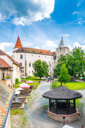 Krivoklat, Czech Republic - 12.6.2020: View of courtyard at castle Krivoklat. Tourist are resting on the grass or bench. View of castle tower. Summer weather, sunny day with clouds.