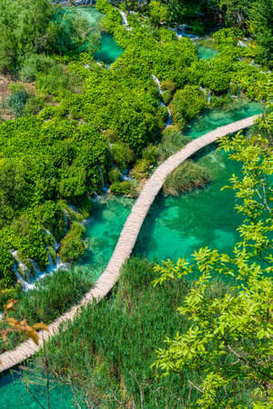 Aerial view of wooden footpath trail at Plitvice lakes, Croatia. Tourist path above lagoon near the waterfalls. Empty bridge without peoples.
