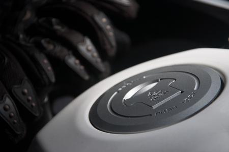 tanque de combustible: tapa de combustible y guantes de motocicleta en un depósito de combustible de una motocicleta.