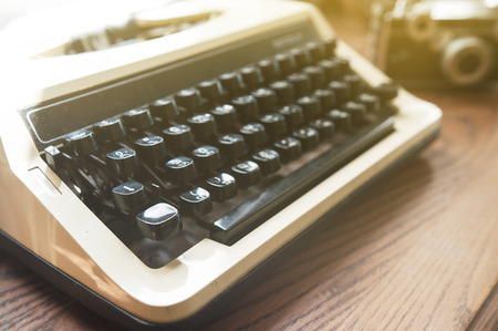 memorise: Close up and soft focus, old typewriter with vintage camera on wood table.