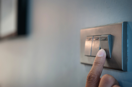 A finger is turning on a light switch. Stockfoto