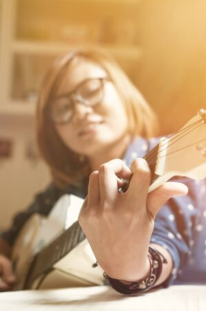 Close up and selective focus, Asian girl is playing the guitar. Stock Photo