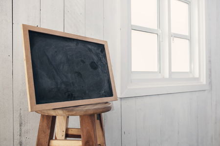 antique sleigh: Foreground dirty chalkboard on round wooden chair,  near a white windowsill and white wooden wall background.