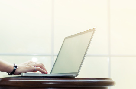 departmentstore: Hand is typing on  laptop on wooden table on white windowsill background.