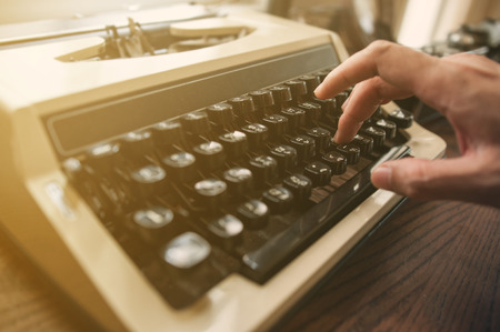 typewrite: Close up, Hand is typing on an old typewriter on wood table. Stock Photo