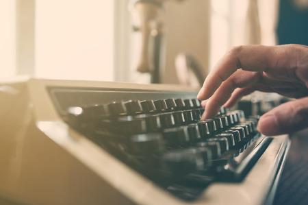 typewrite: Close up, Hand is  typing on an vintage typewriter.