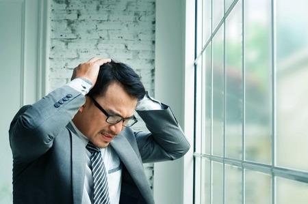 poronienie: Businessman haedache and heart failure when he work hards at his offiice.