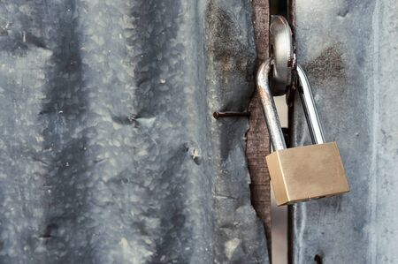 corrugated iron: Close up, Padlock with old corrugated iron fence background. Stock Photo