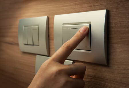 switch: A finger is turning on a grey metallic light switch. Stock Photo