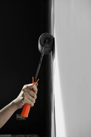 renew.: In the dark mood, Hand holding roller paint applying grey paint on white wall. Copy space.
