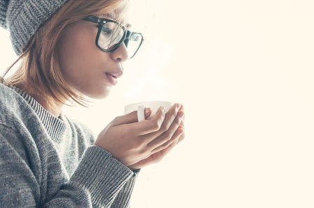 Winter and chistmas holidays concepts, Asian girl in woollen clothing with a cup of hot drink near a windowsill. Archivio Fotografico