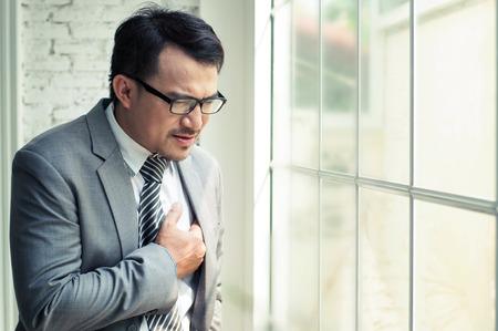 Homme d'affaires soit malade et l'insuffisance cardiaque quand il travaille dur à son bureau.