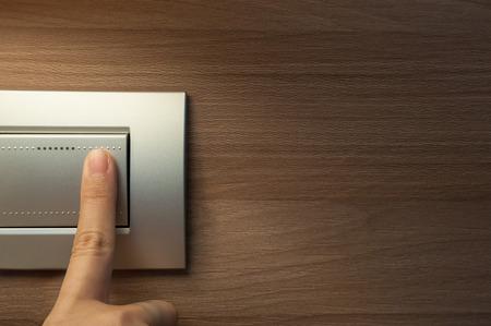 손가락이 회색 금속 조명 스위치를 켜고 있습니다.