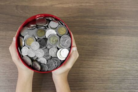 Top view, Money in the red bucket on wooden table background, Kid hands holding a money bucket.