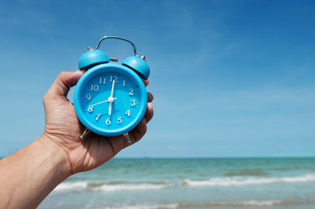 Hand is holding retro alarm clock on sky and sea  background.