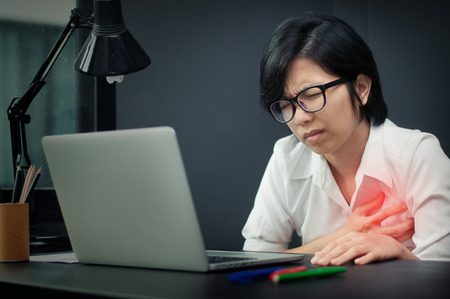 Asian eyeglasses girl  having heart attack. Business woman be ill  at her office. Archivio Fotografico