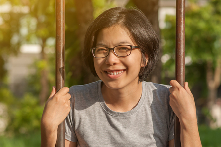 potrait: Potrait of Happiness Asian glasses woman smiling and holding chain of swing at playground. Plants park background. Looking camera.