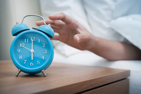 arousing: Woman hand reaching out bed for retro alarm clock. Early morning.