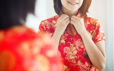 Chinese new year. Asian woman with cheongsam looking  to mirror. Girl is smiling. Get dress.