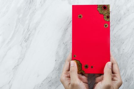 Chinese new year. Woman hand holding red envelope on white marble background. Isolated. Copy space