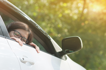 Asian traveler woman resting and living or sleeping in a car on nature background. Happiness of girl on vacation. Closed eyes.