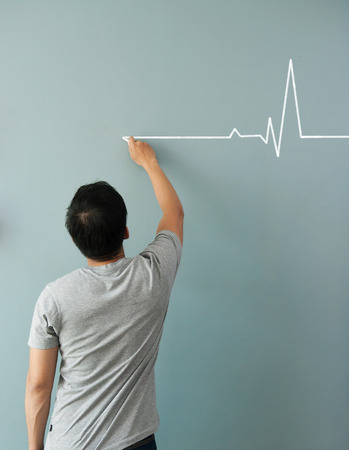 resting heart rate: Man drawing  heartbeat with white chalk on wall. Copy space. wellness concept. Stock Photo