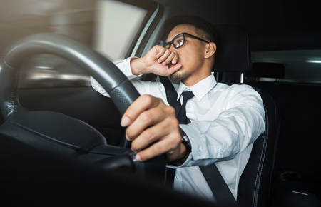 working hours: Asian businessman driving driving a car. Stock Photo