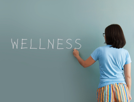 Woman drawing wellness word with white chalk on wall. Stock Photo