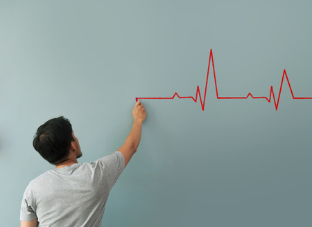 resting heart rate: Man drawing  heartbeat with red chalk on wall. Copy space. wellness concept.