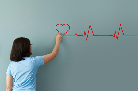 resting heart rate: Woman drawing  heartbeat with red chalk on wall. Copy space. wellness concept. Stock Photo