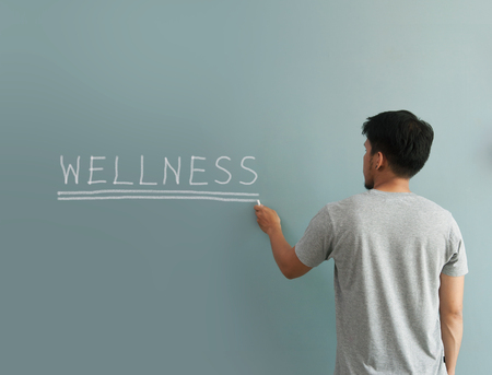 resting heart rate: Man drawing wellness word with white chalk on wall.