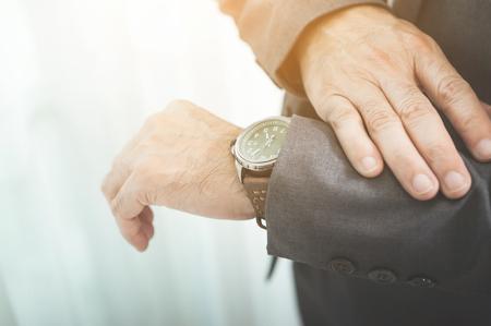 tiedup: Close up of businessman in grey suit looking watch.