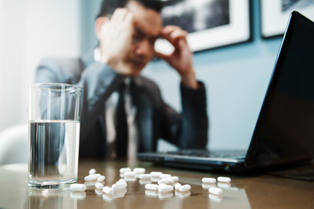 Illness, stressed, tired, exhausted, pain from overworked concepts. Asian Businessman has headache from migraine. Pills with water on foreground. Stock Photo