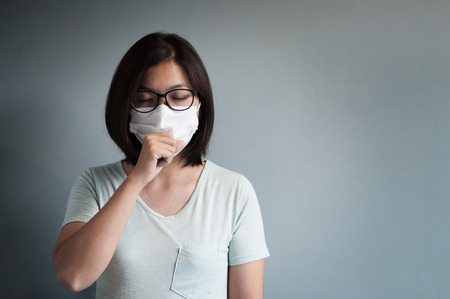 Illness, disease, sick  concepts.  Asian glasses woman has a cold and coughing. Girl with medical mask.