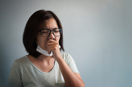 Illness, disease, cold  concepts.  Asian glasses woman has a cold and coughing. Girl with medical mask. Stock Photo