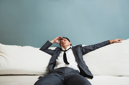 Exhausted, Illness, tired, stressed from overworked concepts. Businessman in grey suit has headache from migraine. Stock Photo