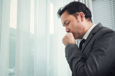 Senior businessman in grey suit coughing. Illness, disease, allergy concepts.