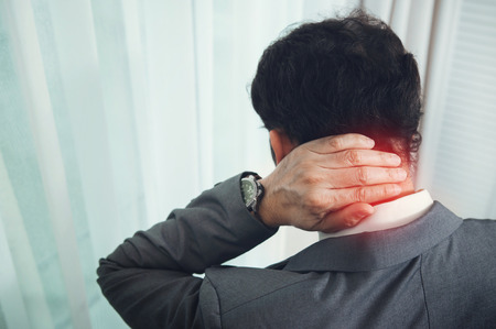 Businessman in grey suit has neck pain. Фото со стока