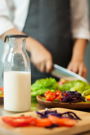 Milk in bottle with woman cooking and vegetables. Stock Photo
