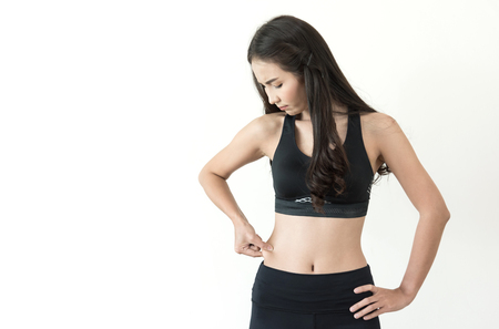 Young Asian woman pinched her belly on white isolated background. Slim girl with copy space. Stock Photo