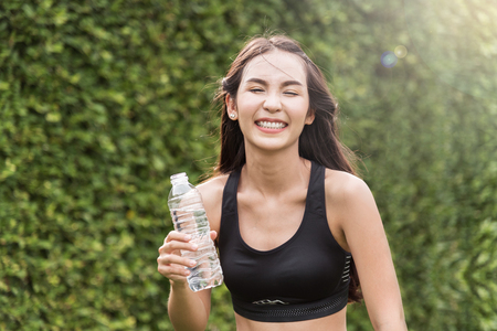 Asian woman holding bottle of water on natural background. freshness, happiness, relaxing and smiling.