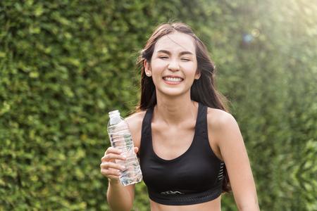 Mujer asiática que sostiene una botella de agua en el ambiente natural. frescura, felicidad, sonriente y relajado. Foto de archivo - 75749478