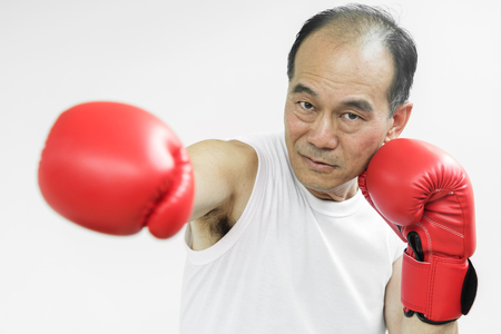 Portrait of Asian senior fighter man punching with red boxing gloves on white background.