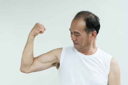 Asian senior man  working out on white background at the gym. copy space.