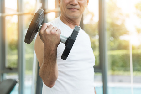 Asian senior man  lifting dumbbells in gym. copy space. 版權商用圖片