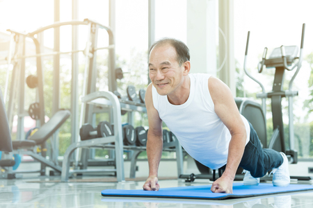 Asian senior man push up at the gym. copy space.